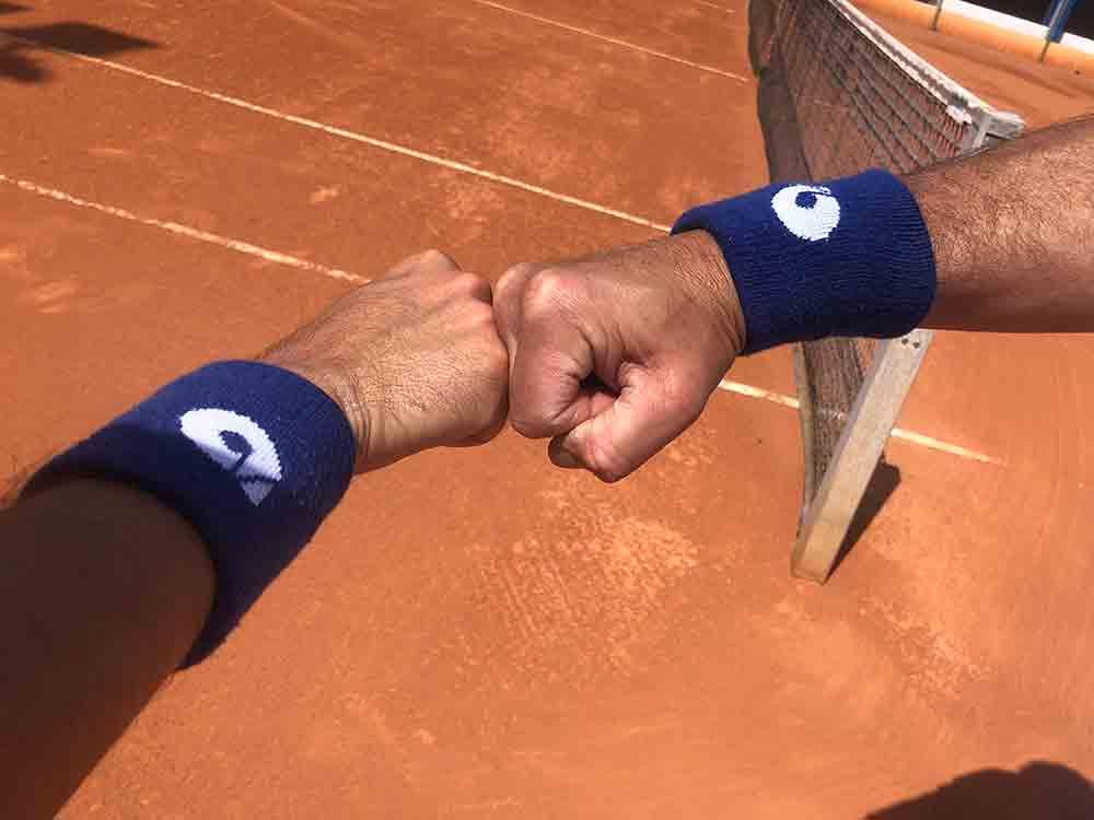 choque de manos en pista de tenis